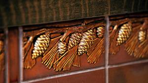 Pine cone fireplace tile detail.